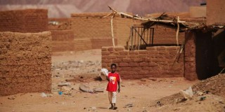 A boy walks past mud brick houses in front of uranium mining byproduct, seen in the background, at Areva's Cominak uranium mine in Arlit, September 25, 2013. Picture taken September 25, 2013. To match Special Report NIGER-AREVA/ REUTERS/Joe Penney (NIGER - Tags: ENERGY ENVIRONMENT SOCIETY) - GM1EA240B2I01
